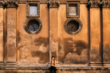 A beautiful girl with long hair stands near the wall of an ancient building and hold hands in her pockets