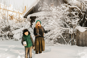 girl and boy playing with snow