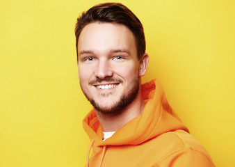 Portrait of a smart young man standing against yellow background