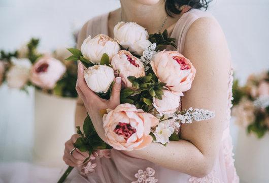 woman is holding flowers in beautiful dress