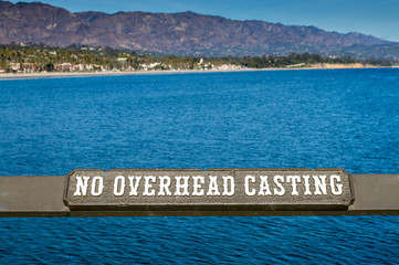 brown wooden 'No Overhead Casting' sign on a fishing pier in Santa Barbara, California with the Santa Ynez mountains in the distance