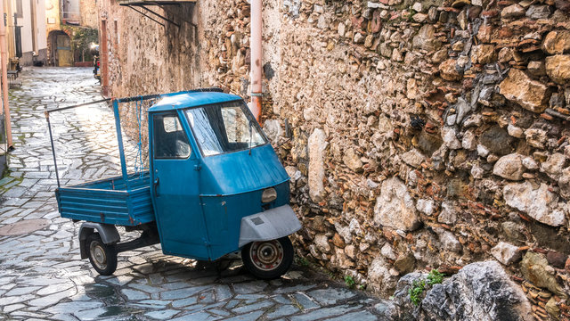 Castelmola, Taormina, Messina. March 2017: traditional vintage vehicle with three weels and blue metal paint, called Ape car,  parked on the street, next to a rural house with big stone wall.