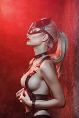 Seductive semi-nude model with leather straps and mask posing in studio