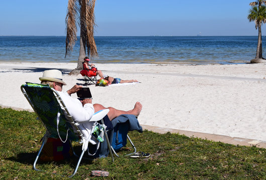 Retired seniors relaxing at the beach, sunny day.
