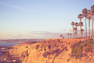 View of beautiful San Diego California seen from Sunset Cliffs in Point Loma with rocky coastline, Pacific Ocean, Palm trees and vintage toned filter.