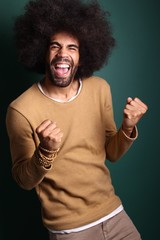 Afro man in front of a green background