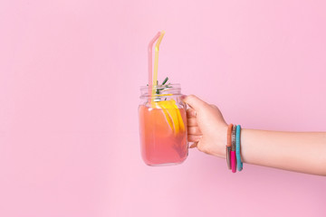 Young woman holding mason jar with lemonade on color background