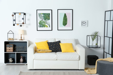 Stylish room interior with tropical leaves and comfortable sofa
