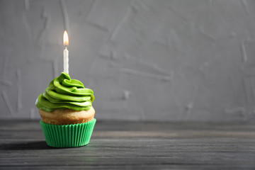 Delicious birthday cupcake with burning candle on table