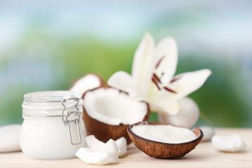 Composition with coconut butter in glass jar and shell on blurred background