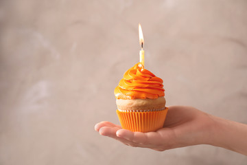 Woman holding birthday cupcake on blurred background