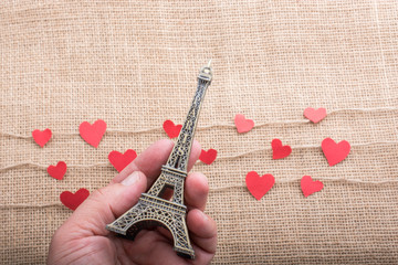 Love concept with Eiffel tower in hand and heart