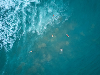 Surfers swim to big wave