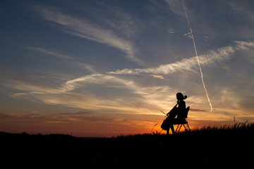 woman playing cello music in a sunset