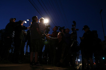 Local resident and bystander holds his son while speaking to the media near the scene of an incident in Austin