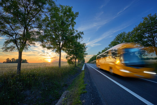 Motion blurred yellow bus traveling on the road in the avenue of trees in a rural landscape at sunset