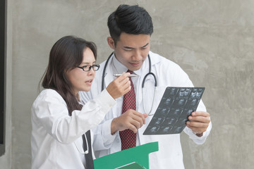 Smart female doctor and smart handsome doctor with stethoscope discuss about film x-ray result, checking a step by step as professional