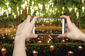 Tourist taking pictures of  Yee Peng Lantern Loy Krathong Festival at Phan Tao temple, Chiangmai, Thailand on smartphone