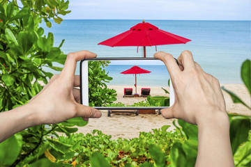 Tourist taking pictures of beautiful beach and red umbrella on smartphone