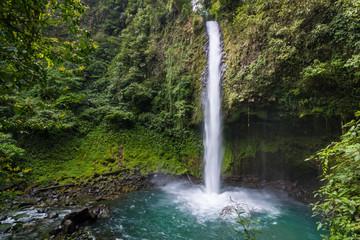 Waterfall into beautiful turquoise pool in Costa Rican rainforest