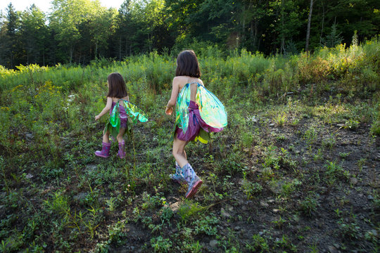 Girls dressed as fairies hiking in the woods