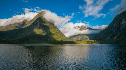 Spectacular mountain range surrounded by clouds close to sunset at Milford Sound