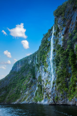 One of the numerous waterfalls falling down the sheer cliffs at Milford Sound in Fiordland National Park, New Zealand