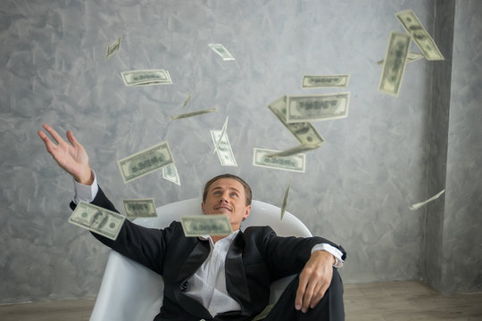 Rich businessman lying in bathtub filled with dollar banknotes. Success business concept.