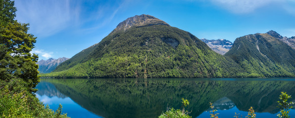 Lake Gunn Panorama with Reflections in Water on the road to Milford Sound in Fiordland National Park, New Zealand.