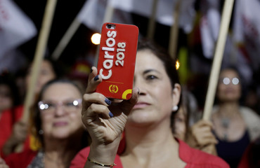 A supporter of Carlos Alvarado, presidential candidate of the ruling Citizens' Action Party, takes a picture with her mobile phone during a campaign rally in San Jose