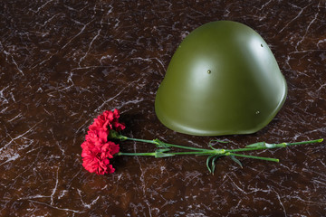 on a marble brown background is a military helmet and red flowers