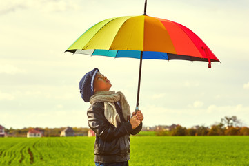 Boy on the field with a bright colorful umbrella . The child enjoys nature