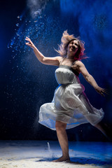 Old fat ballerina tries to dance in the studio during photoshoot with flour on a black background