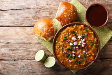Indian Mumbai food Pav bhaji from vegetables with bread close-up in a bowl. horizontal top view