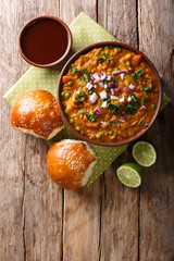 Indian Mumbai food Pav bhaji from vegetables with bread close-up in a bowl. Vertical top view