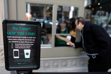 A customer picks-up his smart phone order from a new mobile order window, tested at a Starbucks coffee shop in downtown Los Angeles