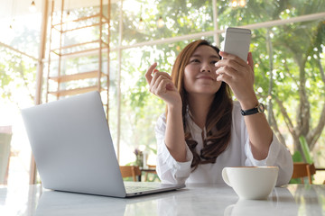 Closeup image of a beautiful Asian woman holding and looking at smart phone while using laptop in cafe