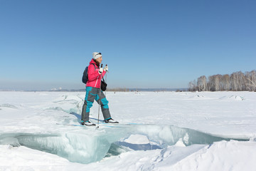 Happy woman skier in a red jacket standing on an ice floe on a frozen river, Ob reservoir, Russia