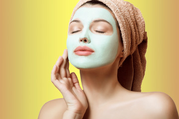 Close-up portrait of a beautiful and well-groomed woman in a towel and with a mask on her face on a multicolored background. Face care. Spa, beauty treatments.