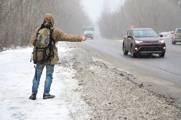A man with a large backpack showing thumbs up for hitchhiking during road trip along a suburban asphalt road in a wintertime blizzard