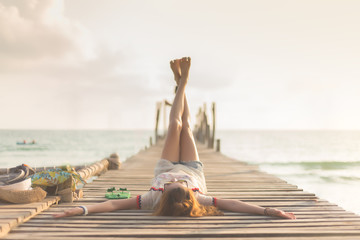Happy young asian woman is lift and cross her leg on wooden bridge pier near the beach during sunset background. - Vintage style and lifestyle for travel concept.
