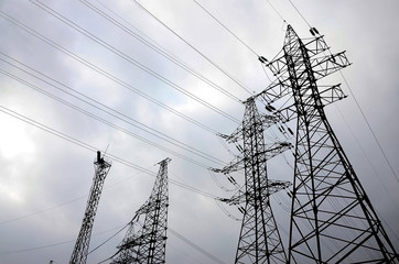 Towers power lines against a cloudy sky background. Electricity transmission pylons