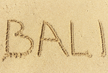 The inscription on the sand of Bali. Vacation time, beach holidays.