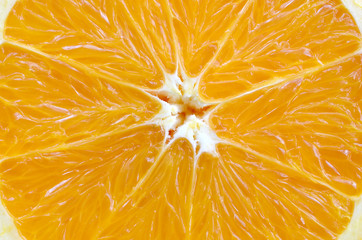 Top view of a fragment of the orange fruit slice close up. Macro background texture