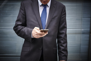 Business man texting with mobile phone. Working time. Outdoors