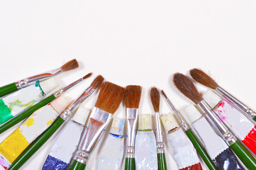 Paint brushes and used color tubes isolated on a  background