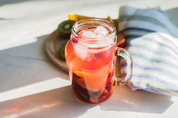 Red fruit homemade lemonade with ice in a jar in the morning in the sun
