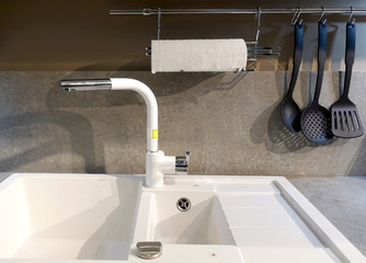 Close-up of a modern kitchen sink and a water faucet on the kitchen countertop.