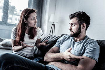 Can you explain. Young worried disturbed couple sitting at home on the sofa looking at each other and having discussion.