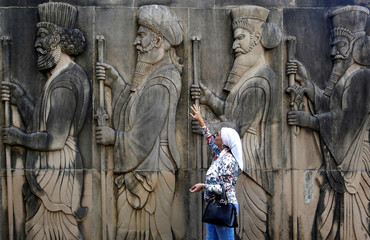 A woman touches the wall of a Parsi fire temple featuring huge carvings of ancient priests on the occasion of the Persian New Year in Mumbai